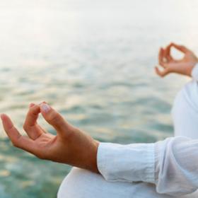 Woman practicing yoga at sunrise